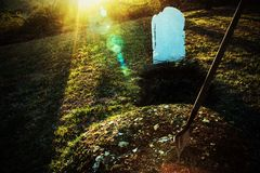 Open grave with shovel at sunset. An open grave with a shovel stuck in a pile of dirt at sunset. Death, the afterlife, Halloween all come to mind stock photos