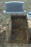 Open grave and tombstone. Freshly dug open grave with blank tombstone royalty free stock photos