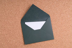 Open Green Envelope with paper on cork background Royalty Free Stock Photo