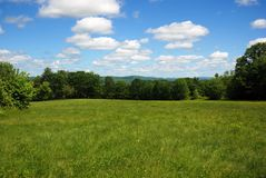 Open green field in New Hampshire on a bright,sunny early summer day. Blue sky, white clouds, bright green grasses, deep green trees Royalty Free Stock Image