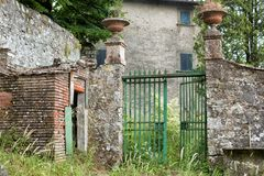 Open green gate at an abandoned Italian Villa. View of an open green gate at an abandoned Italian Villa with overgrown yard, in the tiny rural village of Royalty Free Stock Photography