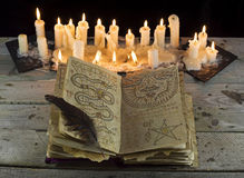 Open Grimoire book with candles. Halloween still life with open black magic book and melting candles Royalty Free Stock Images