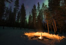 Open haard in het bos met hierboven aurora borealis royalty-vrije stock afbeelding