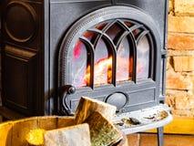 Open haard met brandvlam en brandhout in vatbinnenland heating Stock Afbeeldingen