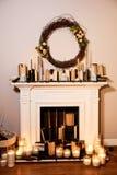 Open haard met kaarsen, de herfstkroon op de muur royalty-vrije stock foto's