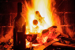 Open haard met wijnglas en fles Stock Fotografie