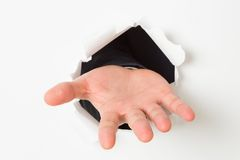 Open hand bursting through paper Royalty Free Stock Photography