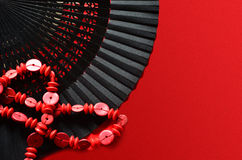 Open hand fan with ornament and red beads. Open hand fan with ornament and beads on red background Stock Photos