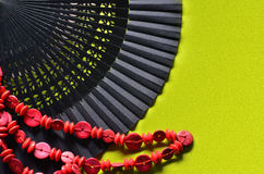 Open hand fan and red beads. Open hand fan and red on a green background Stock Image