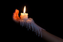 Open hand holding candle stick with wax flowing down the arm Stock Image