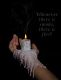 Open hand holding candle stick with wax flowing down the arm Royalty Free Stock Photos