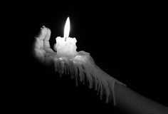 Open hand holding candle stick with wax flowing down the arm art Royalty Free Stock Image