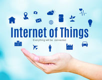 Open hand with Internet of Things (IoT) word and icon on blue blur background Stock Image