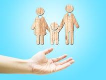 Open hand met houten gelukkig familiepictogram op lichtblauwe achtergrond Stock Fotografie