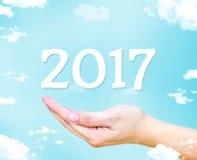Open hand met nieuw het jaaraantal van 2017 bij blauwe hemel en wolk Royalty-vrije Stock Foto's