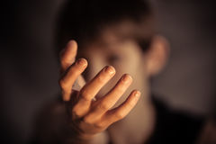 Open hand reaching out from obscured face Royalty Free Stock Photo