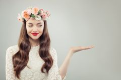 Open Hand van de lente de Modelwoman showing empty met Exemplaarruimte Mooi Meisje met Duidelijke Huid, Krullend Haar, Make-up en stock afbeeldingen