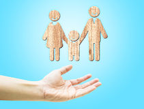 Open hand with wooden happy family icon on light blue background Stock Photography