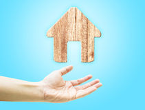 Open hand with wooden plank home icon on light blue background Stock Photo