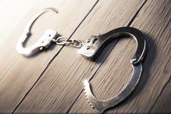 Open Handcuffs op een houten achtergrond Stock Foto's