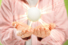 Open hands and golf ball. Open hands with bright golf ball with golden rays. Concept of winner, great play award or luxury sport equipment Stock Photo