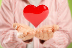 Open hands with heart. Open hands giving big red heart. Concept of pure love or great health Royalty Free Stock Photo
