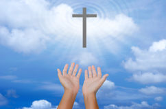 Open hands praying the cross on blur sky background. Open hands praying the cross on blur sky background Royalty Free Stock Photo