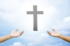 Open hands praying the cross on blur sky background. Open hands praying the cross on blur sky background Royalty Free Stock Images