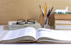 Open hardback or textbook with glasses, and stationary placed on. The table. The concept of intelligence comes from education. Selective focused royalty free stock photo