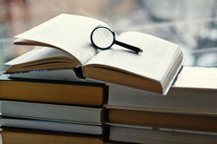 Open hardcover books, magnifying glass Royalty Free Stock Photography