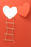 Open Heart. Rope ladder hanging on the wall with open window like a heart made from red paper. With clipping path for your images Royalty Free Stock Images