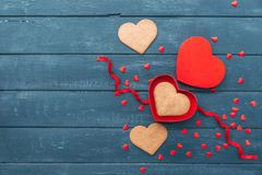 Open heart shape gift box with cookies over wooden background. Happy valentines day. Love background Stock Photo