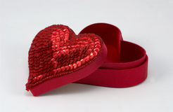Open Heart Shaped Box. Red sequined heart shaped box with the lid positioned slightly off to the side Royalty Free Stock Photography