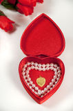 Open heart shaped box with pearls and necklace Stock Photos