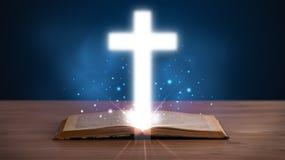 Open heilige bijbel met gloeiend kruis in het midden Stock Afbeeldingen