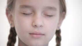 Open het close-up kijkt van Kaukasisch meisje met vlechten die en ogen openen sluiten De neutrale emotie onderzoekt de camera stock video