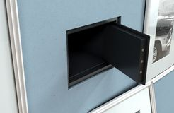 Open Hidden Wall Safe Behind Picture. An open hidden wall safe revealed behind a hanging framed picture on a flat blue wall in a house with shiny wooden floors stock photos