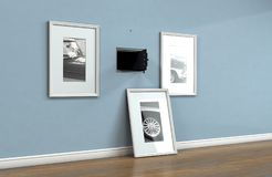 Open Hidden Wall Safe Behind Picture. An open hidden wall safe revealed behind a hanging framed picture on a flat blue wall in a house with shiny wooden floors stock images
