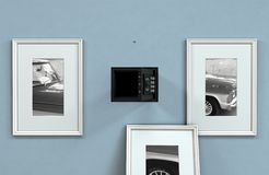 Open Hidden Wall Safe Behind Picture. An open hidden wall safe revealed behind a hanging framed picture on a flat blue wall in a house - 3D render royalty free stock photos