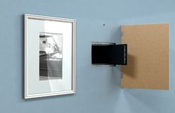 Open Hidden Wall Safe Behind Picture. An open hidden wall safe revealed behind a hanging framed picture on a flat blue wall in a house - 3D render stock photography