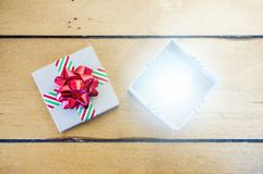 Open holiday gift box with bright light glowing from inside. View from above on old fasioned wooden table. Christmas retail, giving and shopping concept Royalty Free Stock Photos