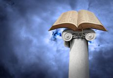 Open holy bible on ancient ionic column pillar post. Photo of an open holy bible resting on an ancient ionic post or column against a heavenly blue sky depicting stock images