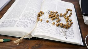 Open Holy Bible on brown wood table background