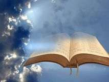 Open holy bible in clouds with sunburst rays light Stock Images