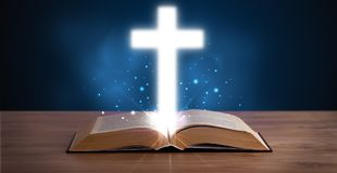 Open holy bible with glowing cross in the middle Stock Image