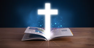 Open holy bible with glowing cross in the middle Royalty Free Stock Images