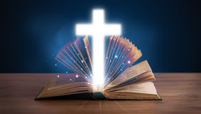 Open holy bible with glowing cross in the middle Stock Photography