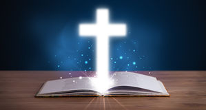 Open holy bible with glowing cross in the middle Stock Photos