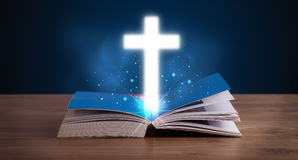 Open holy bible with glowing cross in the middle Royalty Free Stock Photography
