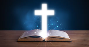 Open holy bible with glowing cross in the middle Stock Images
